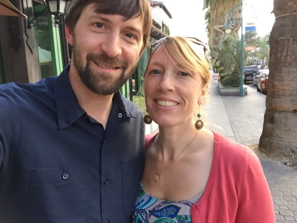 Selfie of Jeff and Andrea on a palm tree lined street in downtown Palm Springs.