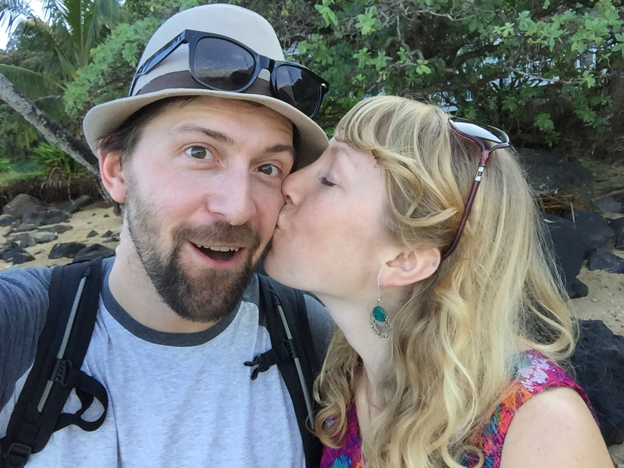 Jeff looking surprised while Andrea kisses him on cheek. They are on a beach in Hawaii.