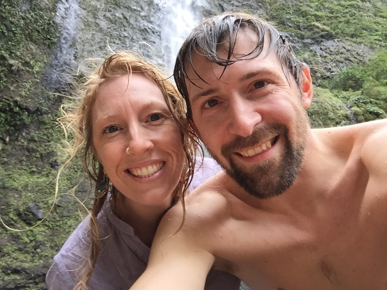Andrea and Jeff in a selfie with the falls and green covered walls behind them.